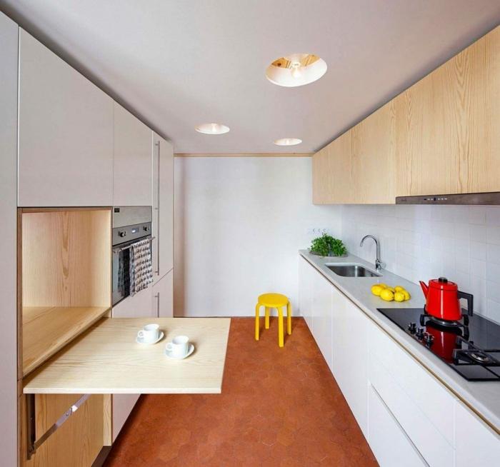 espace aménagé en longueur, cuisine pas cher, carrelage nuances orangées, meuble blanc qui recueille une table pliante en bois clair, plan de travail autour du lavabo en gris perle