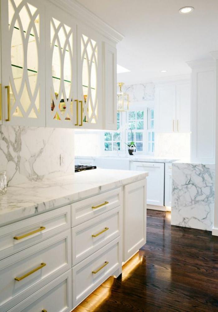 cuisine blanc laqué, meubles rangement suspendus au mur avec vitrine aux ornements arcs entrecroisés, meubles avec des tiroirs larges aux poignées couleur or, parquet en marron
