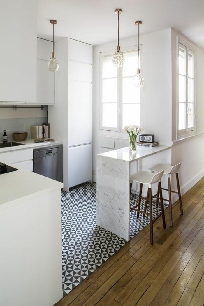 petite cuisine équipée, carrelage blanc et bleu, parquet jaune, luminaires en verre transparent, meubles blancs, tabourets de bar avec des mini-dossiers en plastique blanche et des pieds en bois marron
