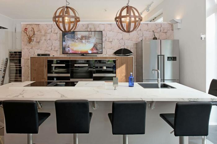 jolie cuisine incorporée, chandeliers rustiques, îlot élégant blanc, grand frigo gris