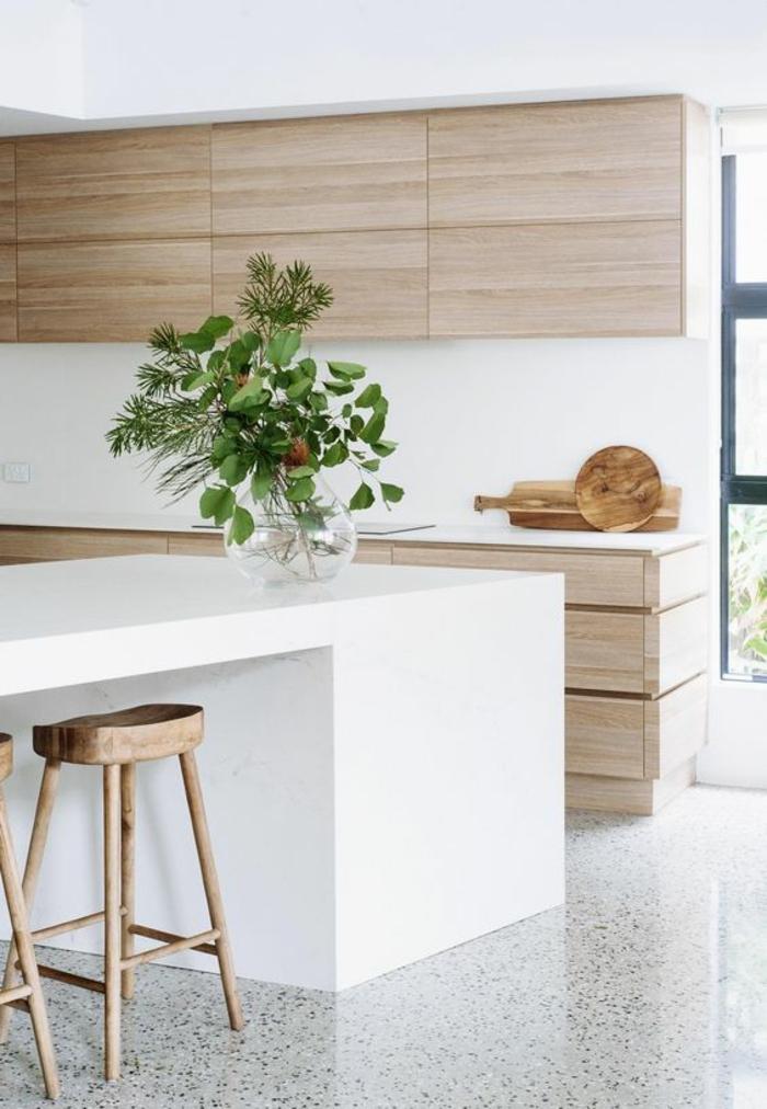 style minimaliste et zen d'amenagement cuisine, cuisine ilot, cuisine laquée blanche, carrelage en gris et blanc, tabourets sans dossiers en bois rude, meubles avec des revêtements en bois clair