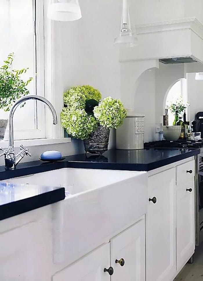 petite cuisine équipée, cuisine noir et blanc, plan de travail noir brillant qui reflète la lumière provenante de la fenêtre, évier couleur argent, plantes vertes dans un vase en cristal en verre fumé