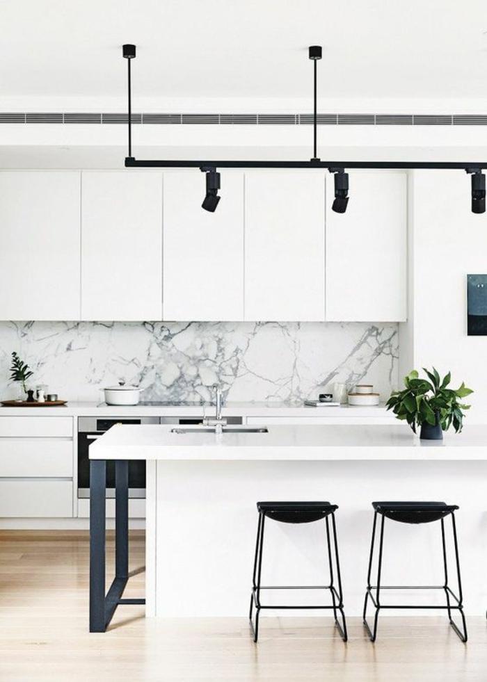 espace en noir et blanc, cuisine laquée blanche, petite cuisine équipée, spots lumineux sur du métal noir au-dessus de l'ilot blanc, parquet clair, tabourets noirs en métal