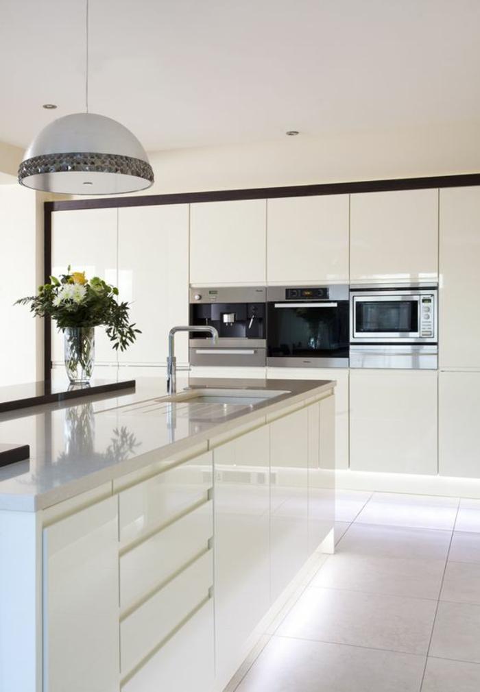 cuisine équipée pas cher, carrelage blanc brillant, luminaire rond avec des éléments décoratifs floraux sur les bords, meubles blancs sans poignées