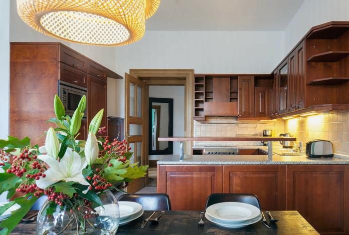 meubles de cuisine en bois, table rectangulaire, lampe tressée, cabinets suspendus