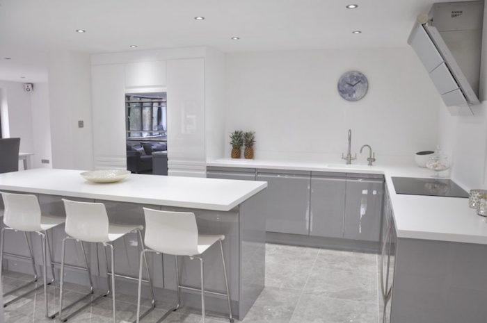 cuisine en l blanche avec ilot et mobilier gris laqué, plan de travail blanc sur gris avec chaise de bar hautes