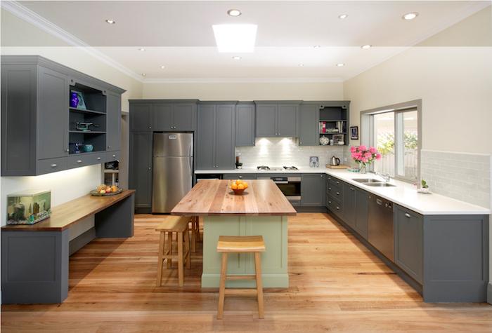 Cuisine équipée grise sur sol en bois, ilot central vert avec meubles gris foncé