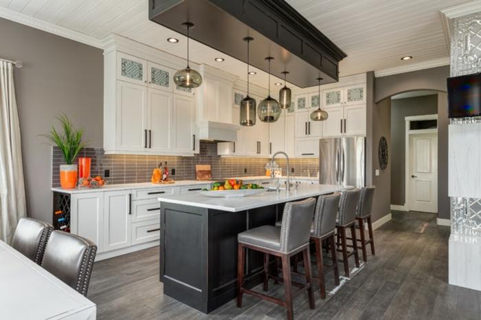 cabinets blancs, ilot de cuisine en noir et blanc, chaises gris et bois, sol contemporain