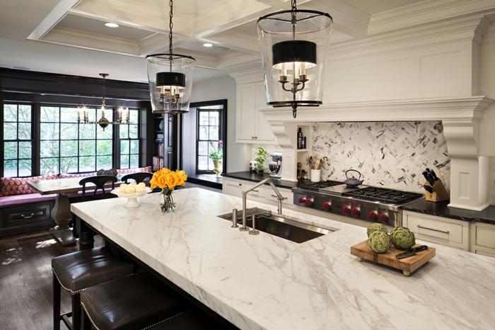 grand ilot de cuisine avec évier, placards peints blancs, banquette près d'une grande porte-fenêtre