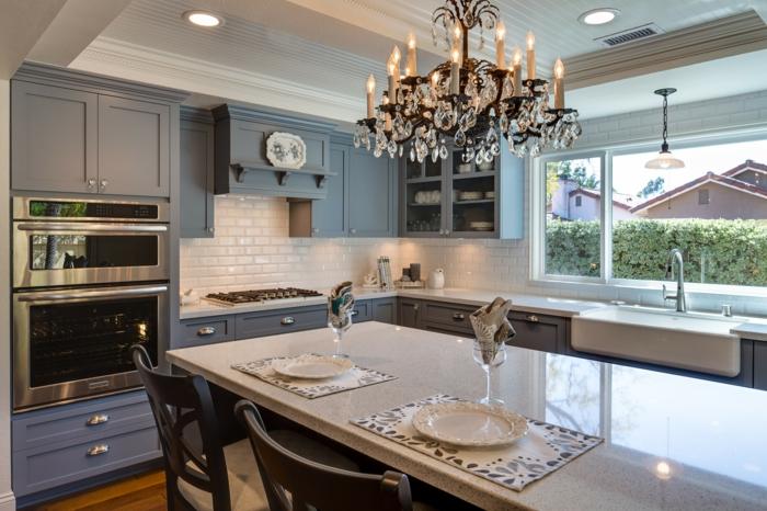 chandelier paraissant luxueux, grande table blanche, appareils électriques intégrés, cabinets bleus
