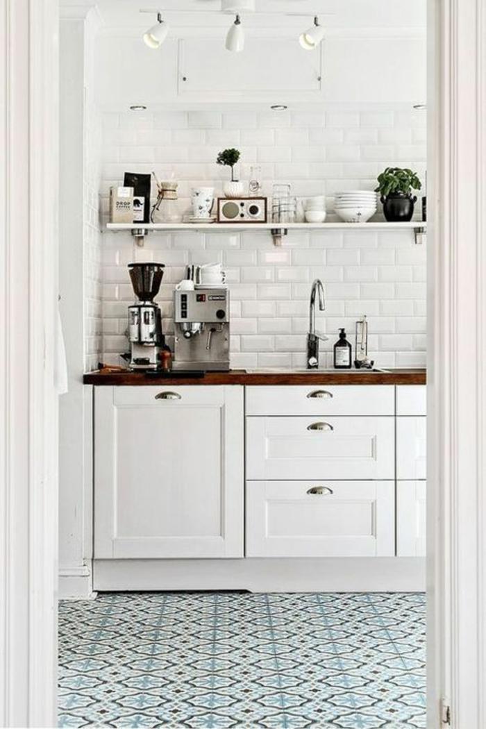 cuisine blanc laqué, carrelage bleu et blanc, murs en briques blanches, spots lumineux mobiles fixés au plafond en métal couleur argent