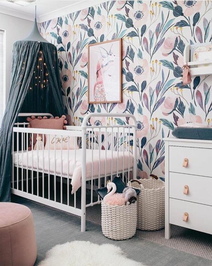 cadre chambre bébé, chambre rose et gris, meuble en bleu pastel, mur avec des grandes fleurs en bleu canard et rose, moustiquaire en bleu pétrole, tabouret rond en rose poudré