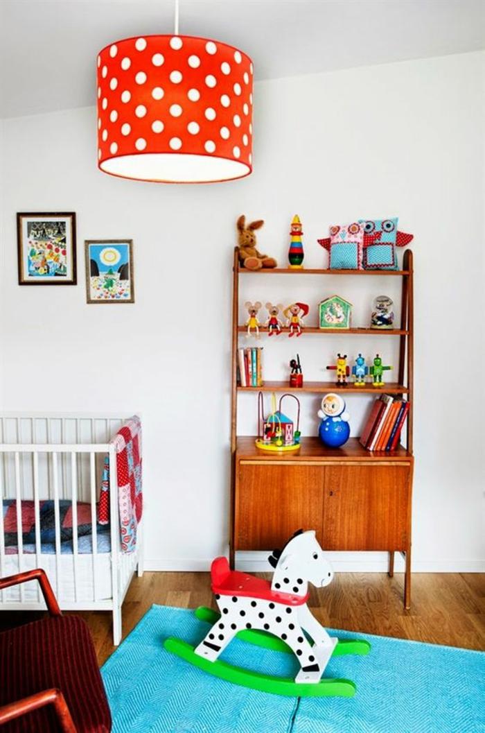 chambre en orange et bleu turquoise, luminaire tambour en orange aux pois blancs, tapis en bleu turquoise, cheval blanc balançoire avec la base en vert pomme, lit blanc, deux tableaux aux cadres marrons, bibliothèque avec des étagères ouvertes, fauteuil en rouge brique