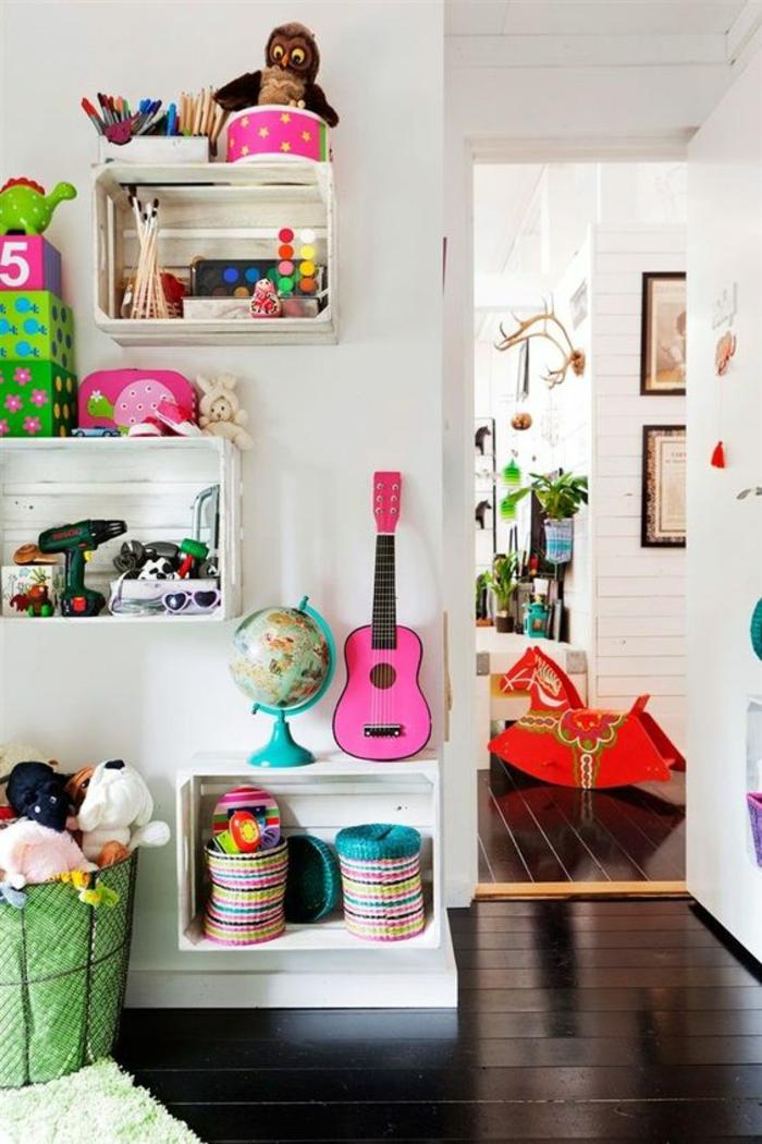 murs blancs, étagères casiers peintes en blanc,plein de jouets sur les casiers, parquet peint en noir, panier en tissu vert pour ranger les jouets