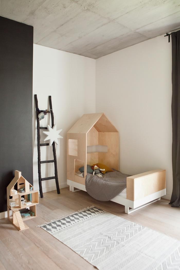 deco chambre fille, aux murs blancs et gris anthracite, échelle décorative en bois rude peint en noir, tapis rectangulaire en gris et blanc, lit-maison en bois clair