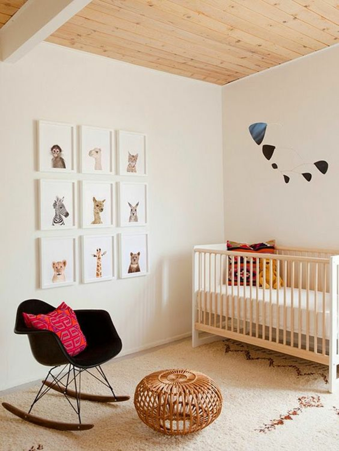 tapis chambre fille en beige et bordeaux, fauteuil basculant en plastique noire avec des pieds en marron foncé, tabouret style pouf en osier, neuf tableaux au mur en cadres blancs, représentant des animaux sympathiques