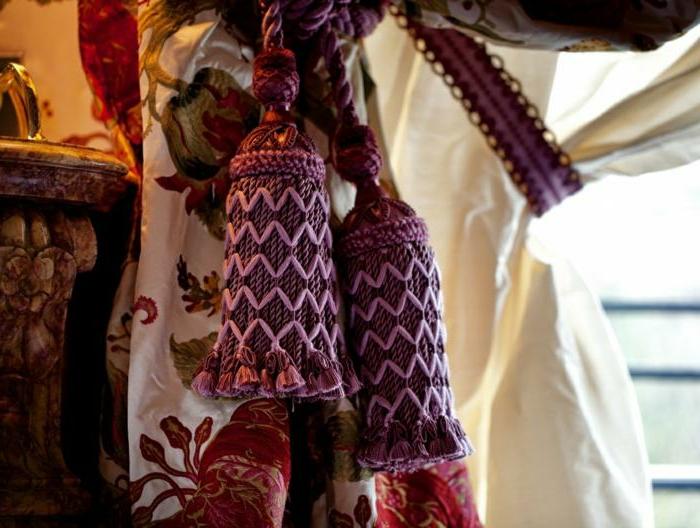 franges pourpres avec des broderies roses sur un rideau blanc, textiles colorés