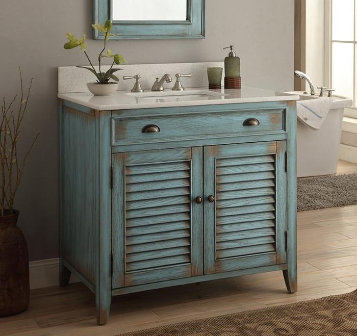 une commode salle de bain à portes persiennes d'un joli aspect vieilli transformée en meuble sous lavabo vintage chic avec une vasque encastrée