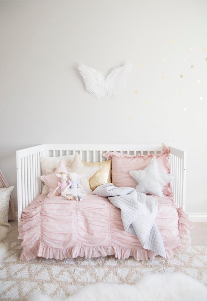 aménagement de chambre enfant fille avec lit bébé de bois blanc, couverture de lit de couleur rose poudré combinée avec coussins en formes étoiles