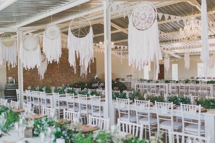 deco mariage style boheme chic, avec des attrape reve geant en dentelle suspendu, chaises blanches, décoration végétation verte