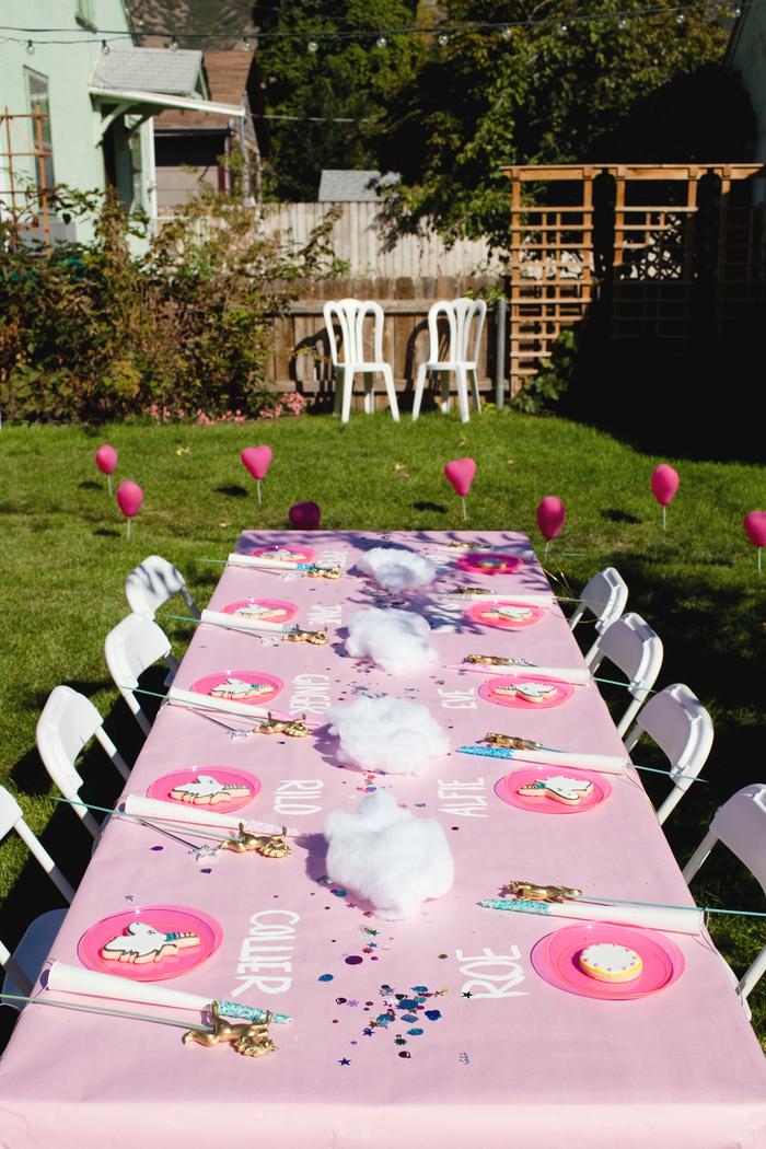 idées déco pour un anniversaire en plein air, jolie décoration de table avec une nappe rose personnalisée avec les noms des invités inscrit dessus et un accessoire licorne près de chaque assiette