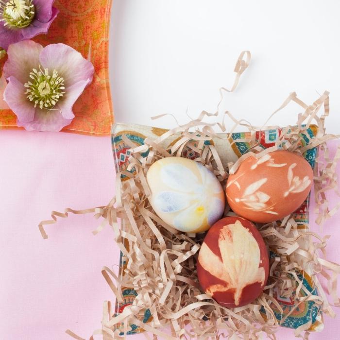nappe en blanc et rose avec assiette à design multicolore et motifs ethniques, exemple d'oeufs colorés aux empreintes végétales