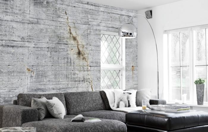 salon blanc et gris avec peinture murale blanche et déco de mur en papier peint à design béton, modèle de canapé d'angle gris combiné avec table de cuir noir