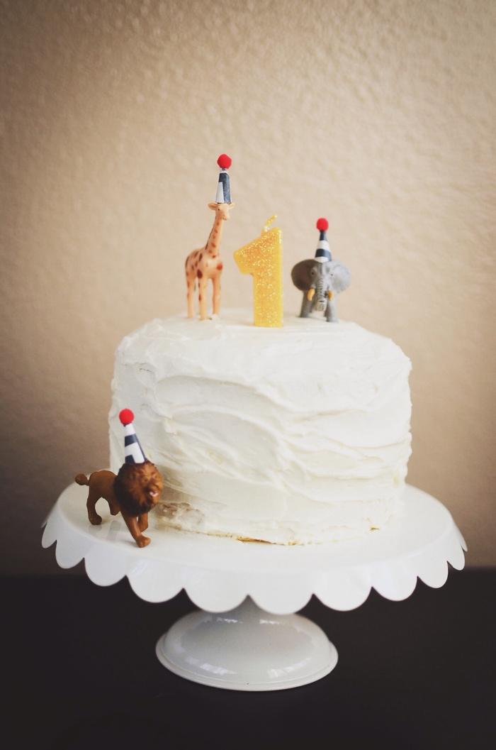 un simple gateau anniversaire 1 an au glaçage au beurre vanille décoré de figurine d'animaux d'afrique idéal pour un anniversaire à thème safari