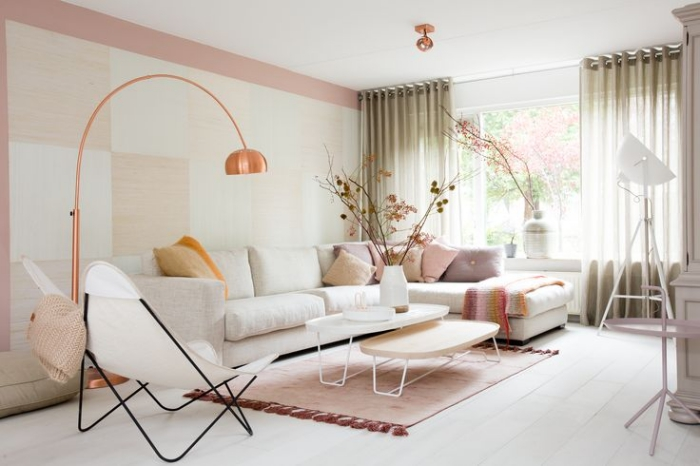 salon aux murs de peinture rose pale combinée avec papier peint à design carreaux beige et vert pastel, modèle de canapé beige d'angle