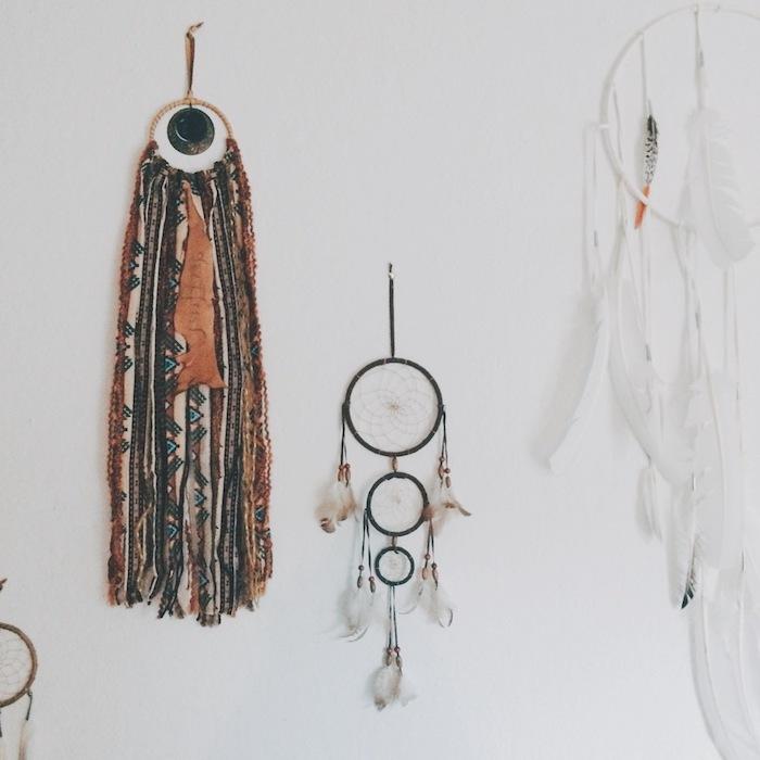 exemple de décoration murale salon en attrape reve traditionnel, attrape rêve tribal en chutes de tissu, et capteur en plumes blanches
