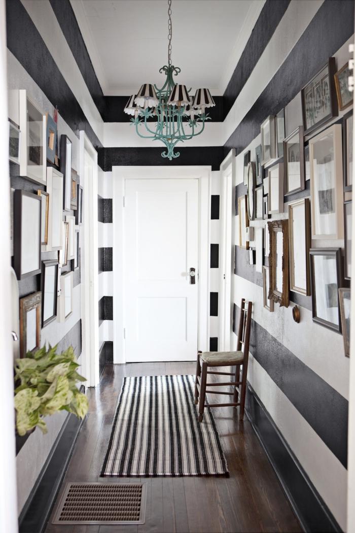 peinture couloir rayée en blanc et noir avec une décoration art de cadres photos à différentes tailles et couleurs