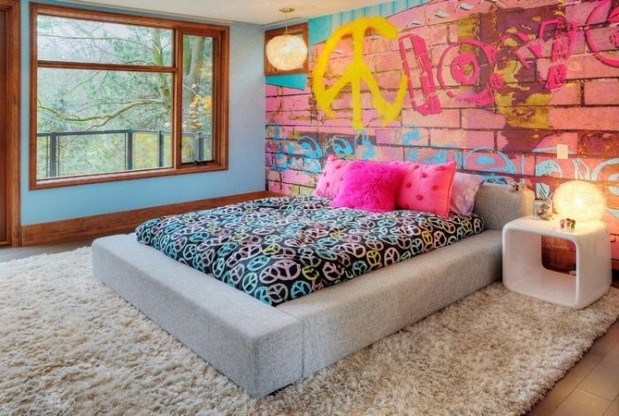 modèle de papier peint chambre ado à design graffiti rose et bleu, aménagement pièce intime avec grand lit et meuble blanc