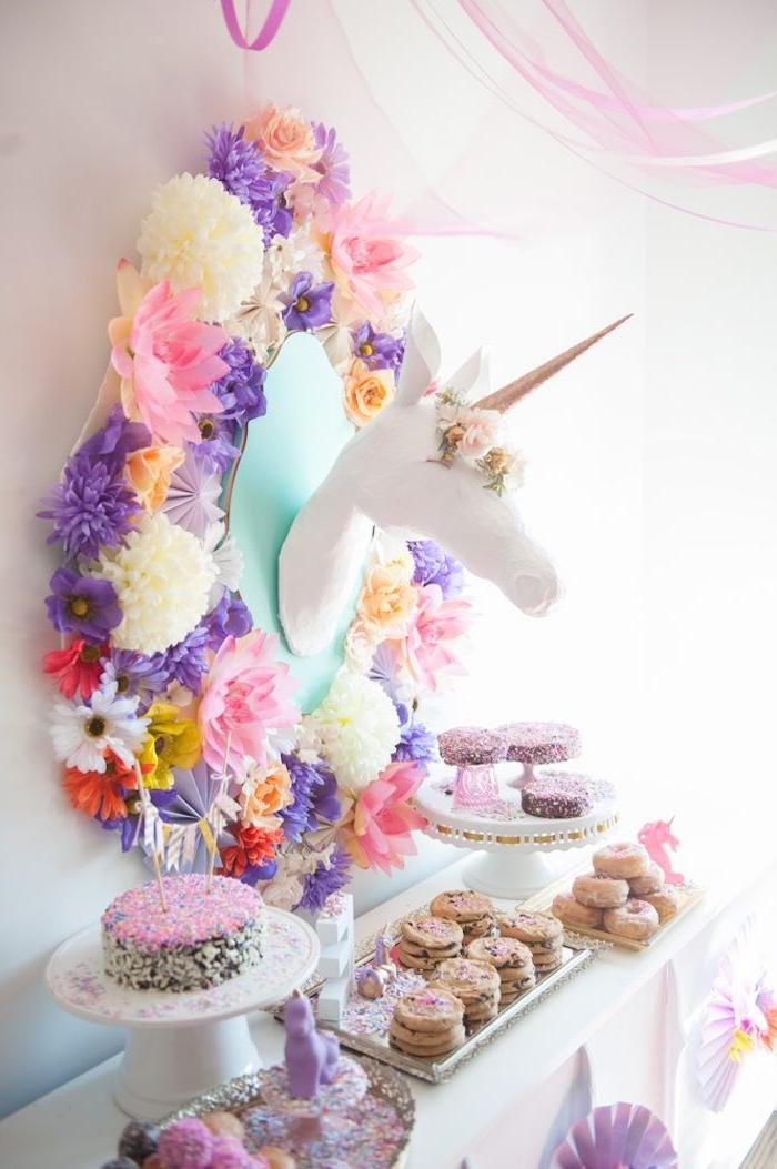 décoration murale tendance avec un objet licorne façon trophée de chasse en carton personnalisée avec des fausses fleurs et une corne dorée