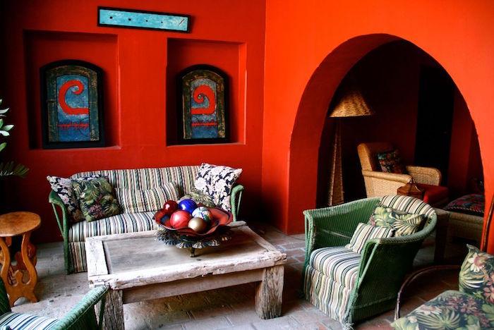 deco de salon type ethnique rustique, decoration boheme provencal avec mur rouge, salon de terrasse en osier vintage