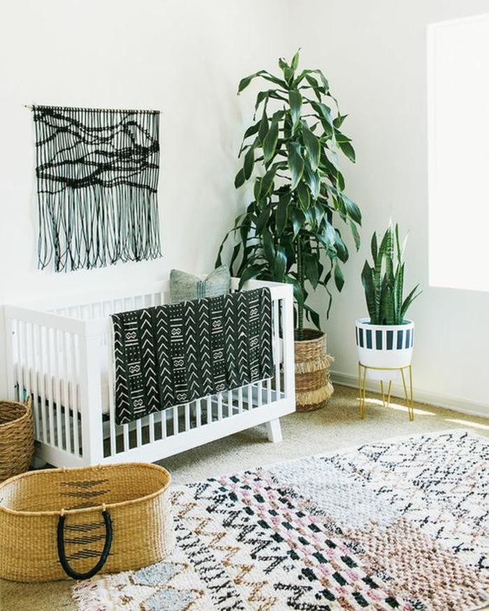 décoration murale en noir avec des longues franges en style boho chic, plantes vertes, tapis en tonalités pastels, lit tout blanc, aménagement et décoration chambre bébé fille en style boho chic