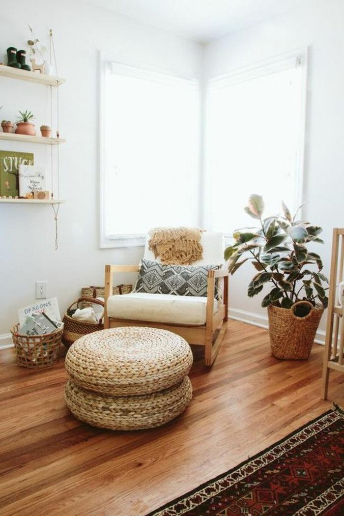 decoration chambre enfant, murs blancs, deux poufs superposés en osier clair, parquet superposé PVC en nuances beige et marron, pot avec plante verte, fauteuil en tissu blanc avec dossier et accoudoirs en bois clair, tapis en rouge et blanc, étagères blanches