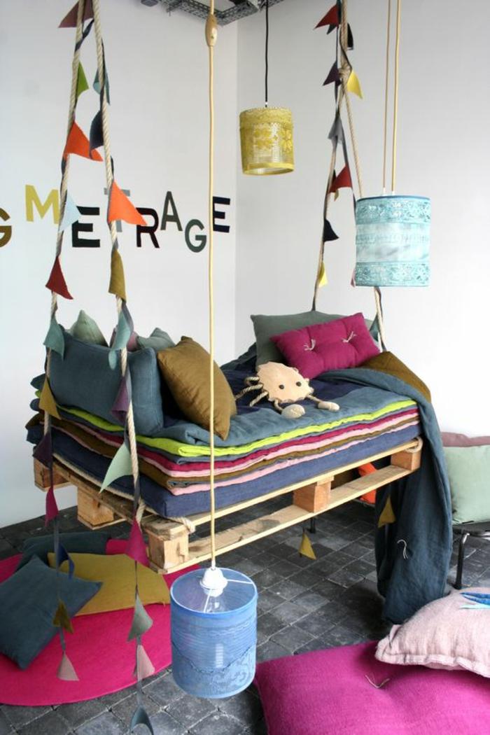 chambre de fille, balançoire suspendue au plafond réalisée avec des palettes, ornée de drapeaux multicolores, carrelage en gris perle, sol recouvert de coussins et de coussinets en couleurs vives