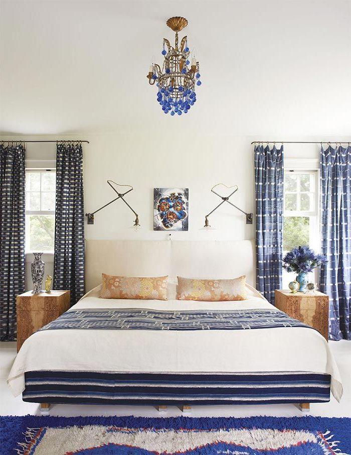 design élégant d'une chambre adulte deco blanc et bleu marine aux motifs graphiques sur le texitle