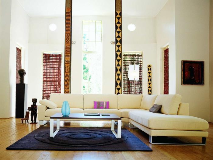 ambiance zen, deco salon zen, tapis en bleu marine avec des cercles sphères, table rectangulaire avec des pieds blancs, parquet jaune, décorations murales en style ethno afro