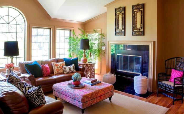 table pouf rose, tapis beige, sofas en cuir, murs en orange pâle, deco ethnique, cheminée murale