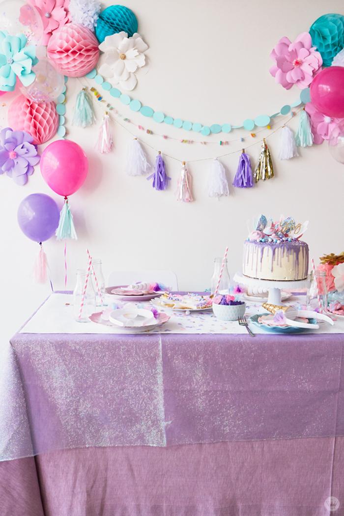 déco licorne aérienne et légère en rose et violet avec une guirlande de fleurs et de boules alvéolées en papier