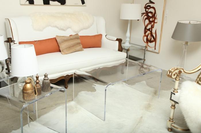 salon feng shui, deco salon zen, tapis au long poil en blanc, deux tables en plexiglas transparent, luminaire tambour avec abat-jour gris, panneau au cadre en bois clair, canapé blanc avec des coussins couleur orange et marron
