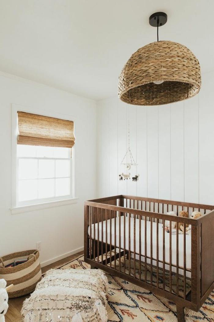 chambre gris et blanc, luminaire rond en rotin tressé,lit en bois marron, fenêtre carrée avec des stores en bambou, tapis en ivoire et en couleurs vives, murs blancs