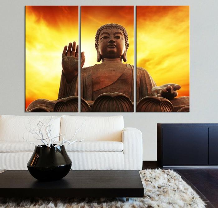 deco epuree, bouddha zen, panneau décoratif avec Bouddha, tapis blanc, table rectangulaire noire avec vase noir qui recueille des branches d'arbre peintes en blanc, canapé blanc
