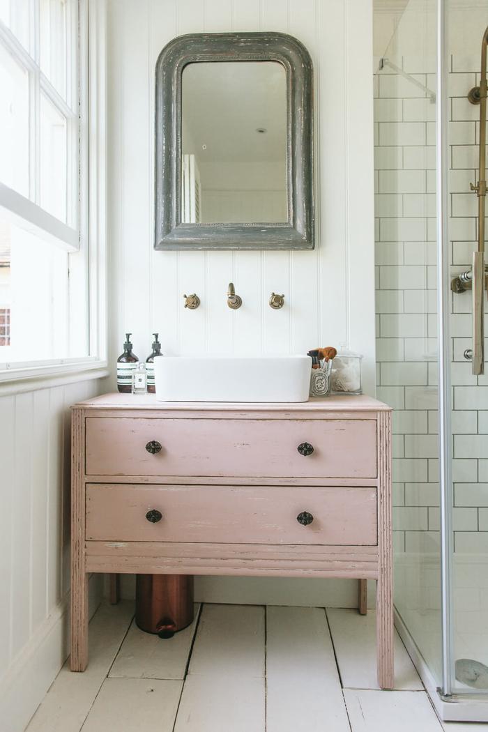 joli coin vasque d'esprit vintage chic avec une commode salle de bain rose à tiroirs, aménagée à côté de la cabine à douche
