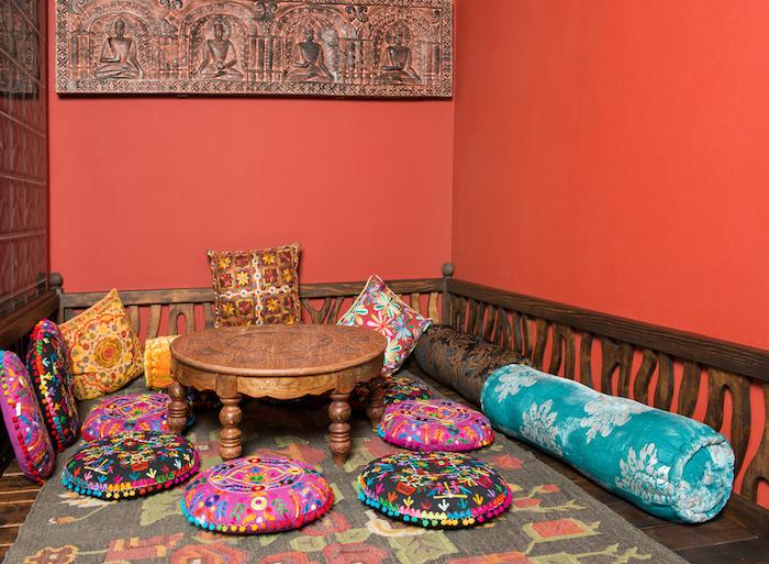 idée deco ethnique chic indienne, salon oriental en bois avec coussins colorés