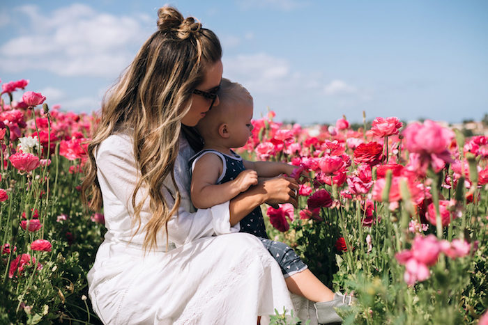 demi chignon haut décoiffé avec des boucles légères, mèches blondes, robe blanche, champs de fleurs, petit garçon