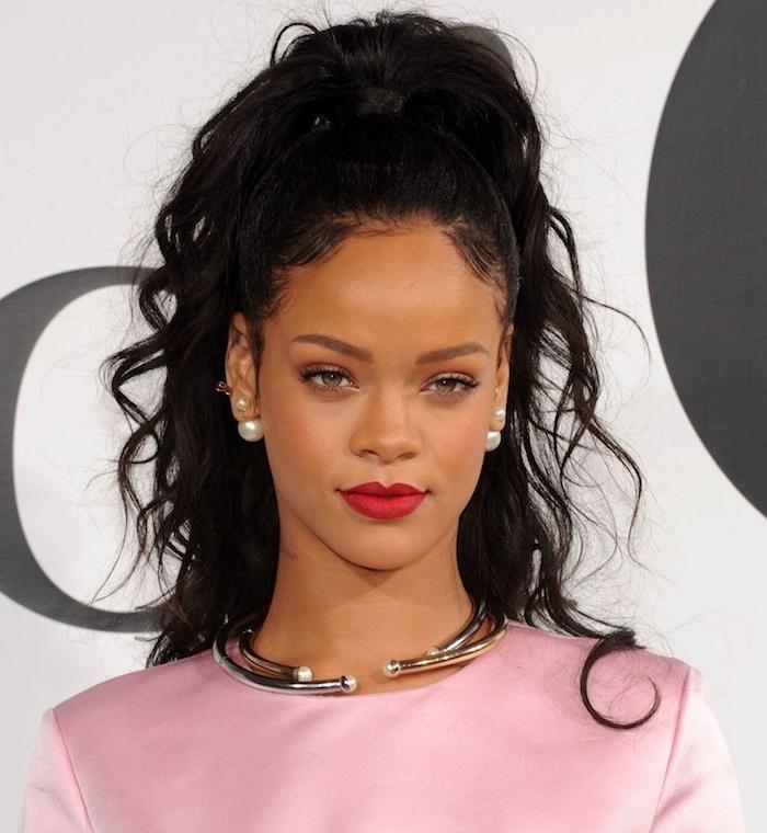 coiffure cheveux bouclés rihanna avec une demi queue de cheval avec boucles, cheveux noirs volumineux, rouge à lèvres rouge, robe rose