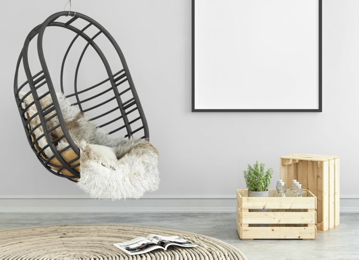 ambiance zen, chaise œuf suspendue en rotin noir, tapis rond en couleur sable, grand cadre en noir, mur en bleu pastel délicat