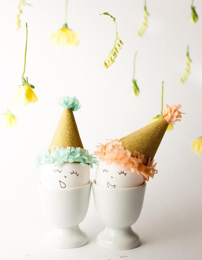 activités manuelles paques, oeufs petits bonhommes dans un coquetier avec des chapeaux en carton à frange de papier coloré, fleurs suspendues